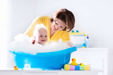 boys and girls: Happy baby taking a bath playing with foam bubbles. Mother washing little boy. Young child in a bathtub. Smiling kids in bathroom with toy duck. Mom bathing infant. Parent and kid play with water. Stock Photo