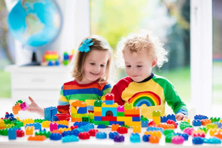Child playing with colorful toys. Little girl and funny curly baby boy with educational toy blocks. Children play at day care or preschool. Mess in kids room. Toddlers build a tower in kindergarten. Stockfoto