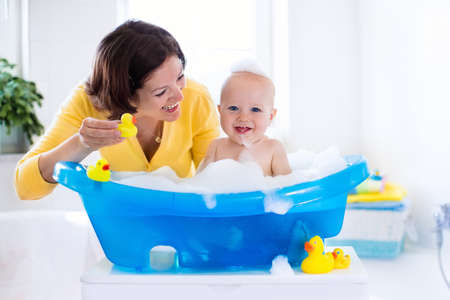 Happy baby taking a bath playing with foam bubbles. Mother washing little boy. Young child in a bathtub. Smiling kids in bathroom with toy duck. Mom bathing infant. Parent and kid play with water. Stock Photo