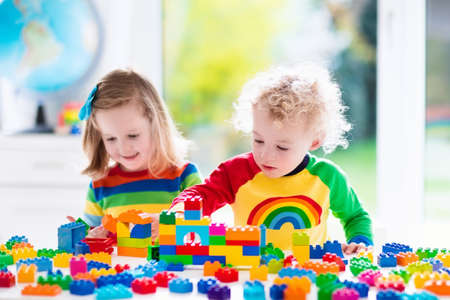 school play: Child playing with colorful toys. Little girl and funny curly baby boy with educational toy blocks. Children play at day care or preschool. Mess in kids room. Toddlers build a tower in kindergarten. Stock Photo
