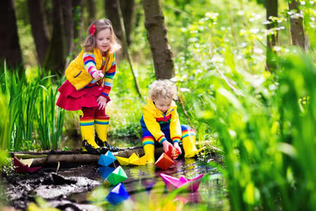 Children play with colorful paper boats in a small river on a sunny spring day. Kids playing exploring the nature. Brother and sister having fun at a forest stream. Boy and girl with toy boat and ship Stock Photo