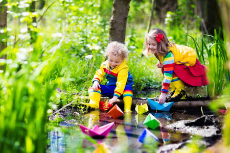 Kinder spielen mit bunten Papierboote in einem kleinen Fluss an einem sonnigen Frühlingstag. Kinder spielen die Erkundung der Natur. Bruder und Schwester, die Spaß an einem Waldbach. Junge und Mädchen mit Spielzeug Boot und Schiff