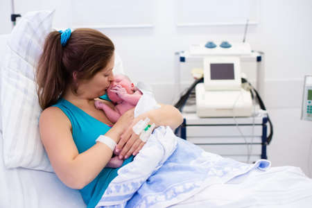 delivery room: Mother giving birth to a baby. Newborn baby in delivery room. Mom holding her new born child after labor. Female pregnant patient in a modern hospital. Parent and infant first moments of bonding.