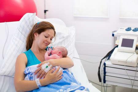 Mutter, die ein Kind zur Welt. Neugeborenes Baby in Kreißsaal. Mom hält ihre Neugeborenen nach der Geburt. Female schwangeren Patientin in einem modernen Krankenhaus. Eltern-Säuglings ersten Momente der Bindung. Standard-Bild