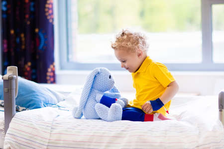 invasive: Little boy playing with his toy in bed in hospital room. Child with IV tube and pulse oximeter in modern clinic. Kid recovering from sickness. Post operative care at children station. Kids health care