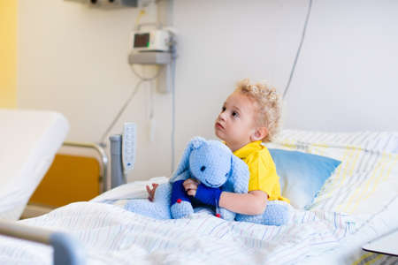 post operative: Little boy playing with his toy in bed in hospital room. Child with IV tube and pulse oximeter in modern clinic. Kid recovering from sickness. Post operative care at children station. Kids health care