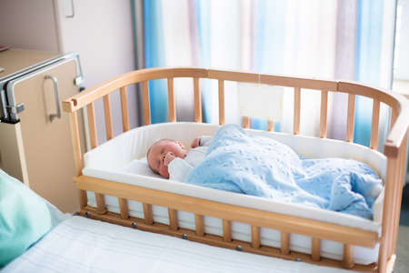 bassinet: Newborn baby in hospital room. New born child in wooden co-sleeper crib. Infant sleeping in bedside bassinet. Safe co-sleeping in a bed side cot. Little boy taking a nap under knitted blanket.
