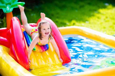 niñas jugando: Los niños que juegan en piscina inflable del bebé. Niños nadar y chapotear en el centro de juegos de jardín colorido. Niña feliz jugando con juguetes de agua en el día caluroso de verano. Familia que se divierte al aire libre en el patio trasero.
