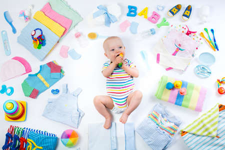 Baby on white background with clothing, toiletries, toys and health care accessories. Wish list or shopping overview for pregnancy and baby shower. View from above. Child feeding, changing and bathing Stockfoto