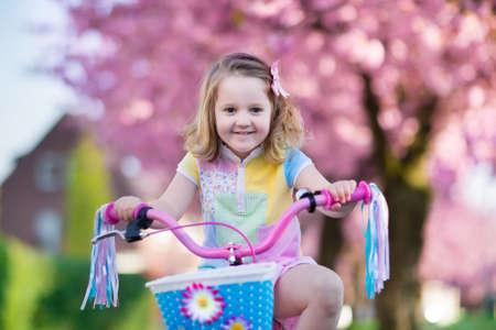 Kinder dem Fahrrad auf einer Straße mit blühenden Kirschbäumen in den Vororten. Kid im Freien im Stadtpark Biken. Kleines Mädchen auf rosa Fahrrad. Gesunde Kinder im Vorschulalter Sommeraktivität. Kinder draußen spielen