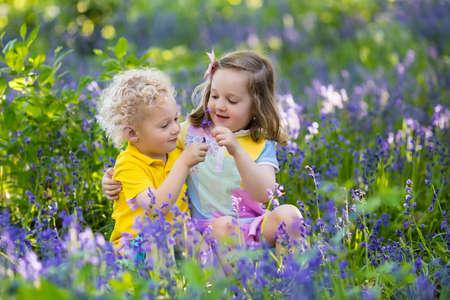 孩子园艺。孩子们在蓝铃嘴草地上玩户外。小女孩和男孩,兄弟和姐妹,在庭院里工作,种植蓝铃花,浇灌的蓝色钟花床。家庭乐趣在夏天。