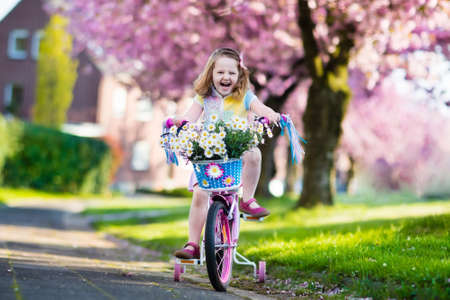street kid: Child riding a bike on a street with blooming cherry trees in the suburbs. Kid biking outdoors in urban park. Little girl on pink bicycle. Healthy preschool children summer activity. Kids play outside