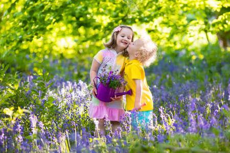 gemelos niÑo y niÑa: Niños jardinería. Los niños juegan al aire libre en el prado campanillas. Niña y niño, hermano y hermana, el trabajo en el jardín, la plantación de flores bluebell, riego azul cama de flor de campana. diversión familiar en verano.