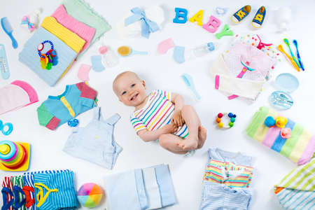 Baby on white background with clothing, toiletries, toys and health care accessories. Wish list or shopping overview for pregnancy and baby shower. View from above. Child feeding, changing and bathing Standard-Bild