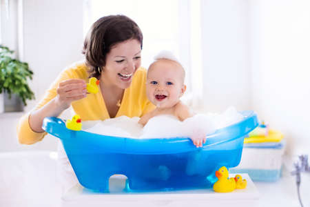 Happy baby taking a bath playing with foam bubbles. Mother washing little boy. Young child in a bathtub. Smiling kids in bathroom with toy duck. Mom bathing infant. Parent and kid play with water. Banco de Imagens - 56545439