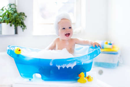 Heureux bébé riant prendre un bain jouant avec des bulles de mousse. Petit enfant dans une baignoire. Sourire enfant dans salle de bain avec coloré jouet canard. le lavage du nourrisson et du bain. Hygiène et soins pour les jeunes enfants. Banque d'images - 56545444