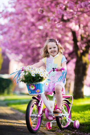 family in park: Child riding a bike on a street with blooming cherry trees in the suburbs. Kid biking outdoors in urban park. Little girl on pink bicycle. Healthy preschool children summer activity. Kids play outside
