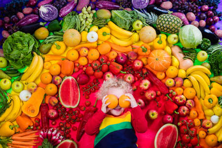 Little boy with variety of fruit and vegetable. Colorful rainbow of raw fresh fruits and vegetables. Child eating healthy snack. Vegetarian nutrition for kids. Vitamins for children. View from above. Stockfoto