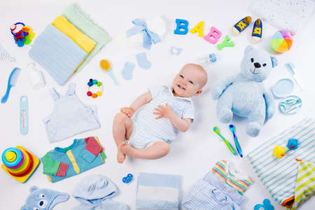 Baby on white background with clothing, toiletries, toys and health care accessories. Wish list or shopping overview for pregnancy and baby shower. View from above. Child feeding, changing and bathing Archivio Fotografico