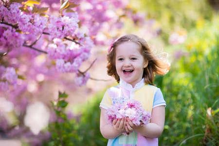 arbol de cerezo: Niña feliz que juega bajo el árbol de cerezo en flor con flores de color rosa. Niño que sostiene la flor de sakura. la diversión de verano para familias con niños al aire libre en un hermoso jardín de primavera. Niño con la flor en Pascua.