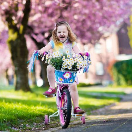 niños en bicicleta: Niño que monta una bicicleta en una calle con árboles de cerezo en flor en los suburbios. Niño en bicicleta al aire libre en el parque urbano. Niña en bicicleta rosada. actividad de verano los niños preescolares sanos. Los niños juegan afuera