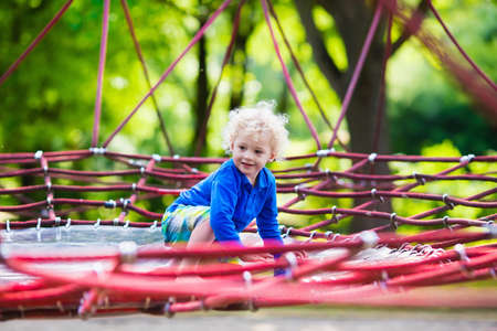 school yard: Active little child playing on climbing net and jumping on trampoline at school yard playground. Kids play and climb outdoors on sunny summer day. Funny boy on nest swing at preschool sport center.