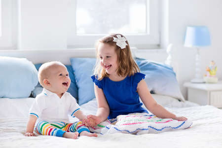 Little girl and baby boy, brother and sister playing in parents bed. Family with children in the morning. Kids play in white bedroom. Nursery crib bedding and textile for young child. Siblings love. Stock Photo