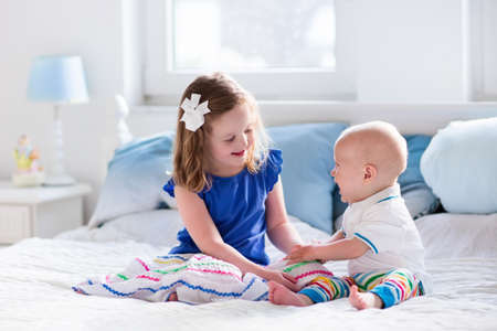 Little girl and baby boy, brother and sister playing in parents bed. Family with children in the morning. Kids play in white bedroom. Nursery crib bedding and textile for young child. Siblings love. Stock Photo - 57560027