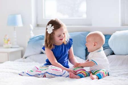 Meisje en baby jongen, broer en zus spelen in het bed van de ouders. Gezin met kinderen in de ochtend. Kinderen spelen in het wit slaapkamer. Nursery wieg beddengoed en textiel voor jong kind. Broers en zussen houden.
