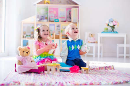 for children toys: Kids playing with doll house and stuffed animal toys. Children sit on a pink rug in a play room at home or kindergarten. Toddler kid and baby with plush toy and dolls. Birthday party for little child. Stock Photo