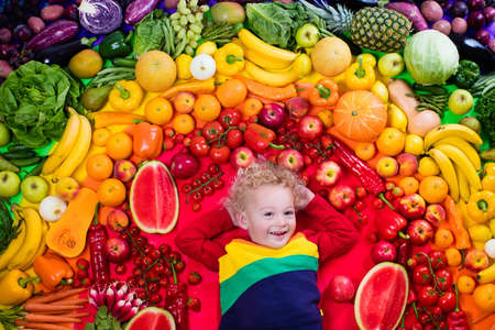 Little boy with variety of fruit and vegetable. Colorful rainbow of raw fresh fruits and vegetables. Child eating healthy snack. Vegetarian nutrition for kids. Vitamins for children. View from above. Фото со стока