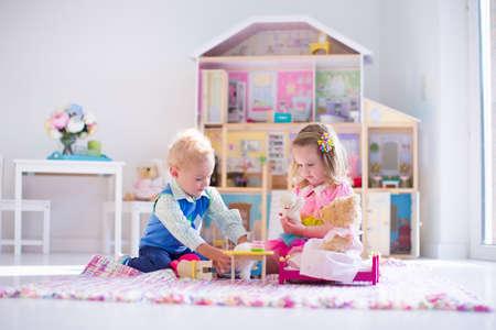 Niños jugando con casa de muñecas y juguetes de peluche. Los niños se sientan en una manta de color rosa en una sala de juegos en la casa o el jardín de infantes. Niño niño y el bebé con el juguete de felpa y muñecas. Fiesta de cumpleaños de niño pequeño. Foto de archivo - 57560243