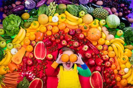 Meisje met verscheidenheid van fruit en groente. Kleurrijke regenboog van rauwe verse groenten en fruit. Kinderen eten gezonde snack. Vegetarische voeding voor kinderen. Vitaminen voor kinderen. Van bovenaf te bekijken.