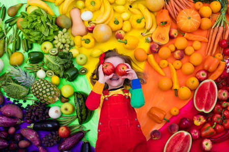 다양 한 과일 및 야채 어린 소녀입니다. 원시 신선한 과일과 채소의 화려한 무지개입니다. 건강 한 간식을 먹는 아이. 아이들을위한 채식주의 영양. 어