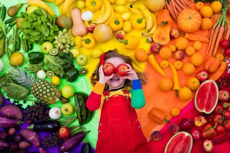 Niña con la variedad de frutas y verduras. Arco iris de colores de las frutas frescas y verduras crudas. Niño que come el bocado sano. la nutrición vegetariana para los niños. Vitaminas para niños. Vista desde arriba. Foto de archivo