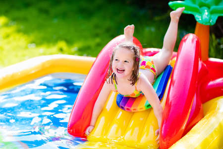 slide: Children playing in inflatable baby pool. Kids swim and splash in colorful garden play center. Happy little girl playing with water toys on hot summer day. Family having fun outdoors in the backyard.