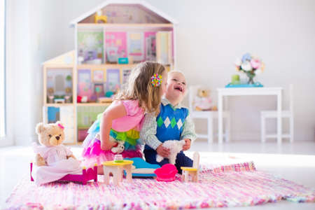 stuffed animals: Kids playing with doll house and stuffed animal toys. Children sit on a pink rug in a play room at home or kindergarten. Toddler kid and baby with plush toy and dolls. Birthday party for little child. Stock Photo