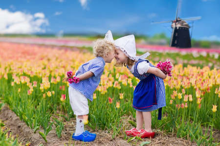 Gelukkig Nederlandse kinderen spelen in bloeiende tulp bloemen veld. Jongen en meisje dragen van traditionele klederdracht, klompen en hoed spelen met tulpen naast een windmolen in Holland, Nederland Stockfoto