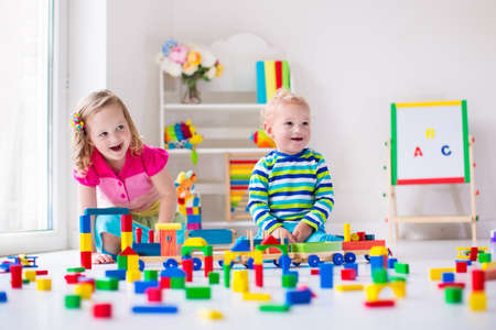 Kinderen spelen op dag zorg. Twee peuter kinderen te bouwen toren van kleurrijke houten blokken. Kind spelen met speelgoed trein. Educatief speelgoed voor voorschoolse en kleuterschool.