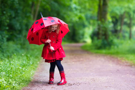 Bambina che gioca nel parco d'estate piovosa. Bambino con l'ombrello rosso coccinella, cappotto impermeabile e stivali saltando in pozzanghera di fango e sotto la pioggia. Kid a piedi in autunno doccia. divertimento all'aria aperta con qualsiasi condizione atmosferica.