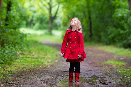 mud girl: Little girl playing in rainy summer park. Child with red ladybug umbrella, waterproof coat and boots jumping in puddle and mud in the rain. Kid walking in autumn shower. Outdoor fun by any weather.