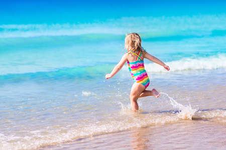 niño corriendo: El niño feliz corriendo y saltando en las olas durante las vacaciones de verano en la playa tropical exótica. De vacaciones en la costa del océano para familias con niños pequeños. Los niños juegan en el mar. Niña aprender a nadar.