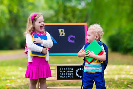 first day: Children happy to be back to school. Preschooler girl and boy with backpack and books at black chalk board learning to write letters and read. Kids at preschool or kindergarten learn the alphabet. Stock Photo