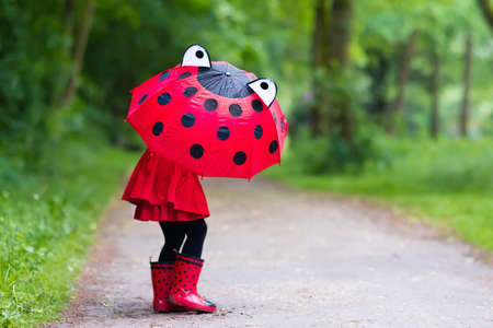 red umbrella: Little girl playing in rainy summer park. Child with red ladybug umbrella, waterproof coat and boots jumping in puddle and mud in the rain. Kid walking in autumn shower. Outdoor fun by any weather.