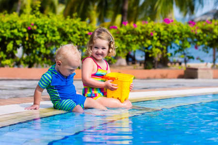 asia children: Girl and boy playing in swimming pool in tropical resort. Child learning to swim. Toddler kid with toy bucket and watering can. Summer beach vacation for family with children. Water fun for kids.