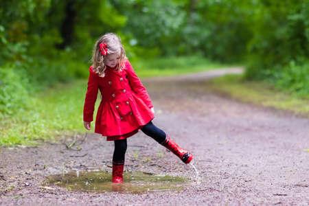비오 여름 공원에서 노는 어린 소녀. 빨간 무당 벌레 우산, 방수 코트와 부츠 웅덩이와 진흙 속에 비에서 점프. 아이가 샤워에서 산책입니다. 날씨에 관