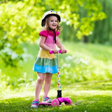 patada: El pequeño niño que está aprendiendo a andar en scooter en un parque de la ciudad en un día soleado de verano. niña de edad preescolar lindo en el casco de seguridad montado en un rodillo. Los niños juegan al aire libre. ocio activo y el deporte al aire libre para los niños.