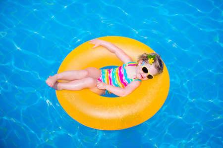 Bambina che gioca nella piscina all'aperto in località tropicale. Bambino imparare a nuotare. kid bambino con anello gonfiabile giocattolo. Estate vacanza al mare per famiglie con bambini. acqua divertimento per i bambini.