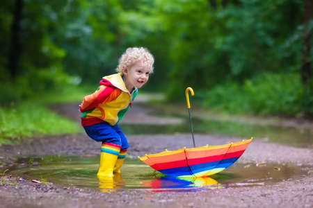 wet clothes: Little boy playing in rainy summer park. Child with colorful rainbow umbrella, waterproof coat and boots jumping in puddle and mud in the rain. Kid walking in autumn shower. Outdoor fun by any weather Stock Photo