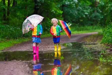 Weinig jongen en meisje spelen in de regenachtige zomer park. Kinderen met kleurrijke regenboog paraplu, waterdichte laarzen springen in plas en modder in de regen. Kinderen lopen in de herfst douche. Outdoor plezier door alle weersomstandigheden